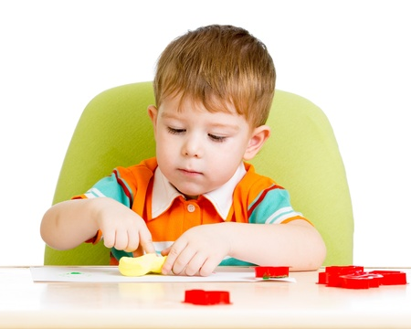 Happy little kid sitting at table and playing with colorful clay toy photo