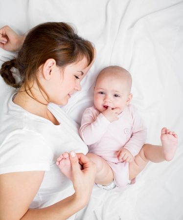 babies hands: joyful mother playing with her baby infant