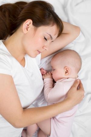 madre y bebe: Madre joven y su bebé durmiendo juntos