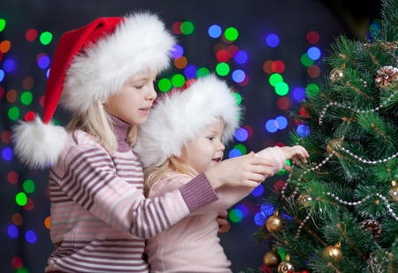 children sisters in Santa Claus hats on bright festive background photo