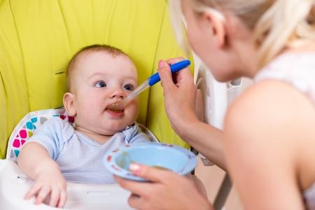 mother spoon feeding her baby boy Stock Photo - 16253604