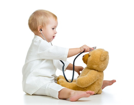 doctor toys: girl with clothes of doctor and teddy bear isolated on white