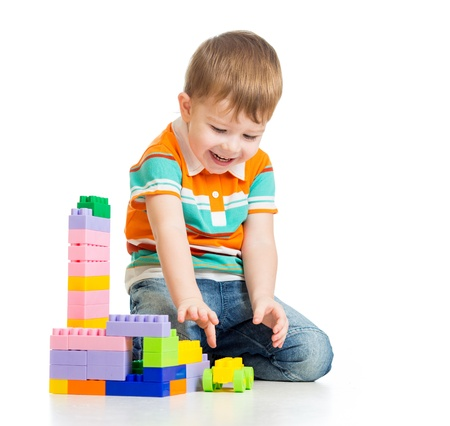 happy child boy playing with construction set over white background photo