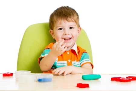 Happy child boy sitting at table and playing with colorful clay toy photo