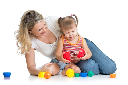 child care: kid girl and mother playing together with cup toys Stock Photo