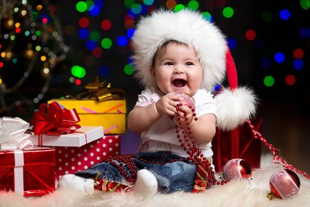 funny baby dressed in Santa Claus hat on bright festive background photo
