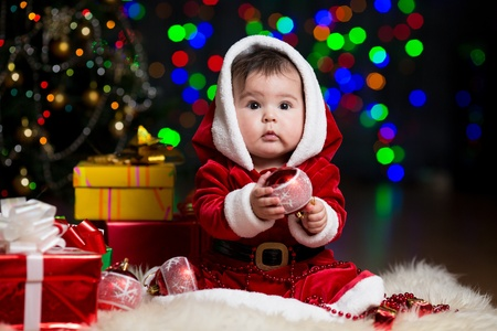 christmas eve: kid girl dressed as Santa Claus near Christmas tree with gifts