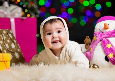 baby near christmas tree: smiling baby girl near Christmas tree with gifts