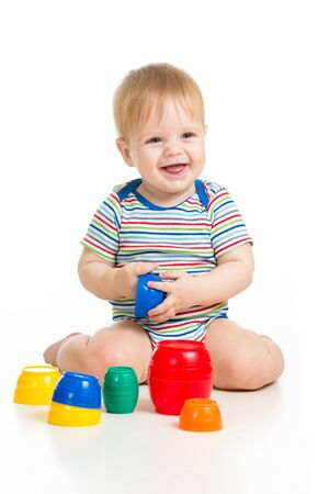 cute baby: Cute little child is playing with toys while sitting on floor, isolated over white