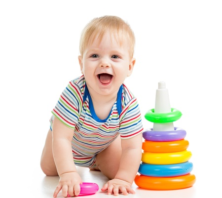 babies with toys: hapy baby boy playing with colorful toy isolated on white Stock Photo