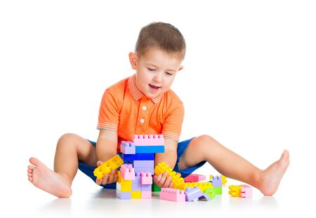 assiduous: cheerful child boy with construction set over white background