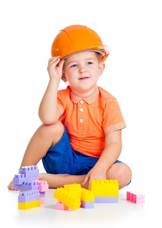 cheerful child boy with hard hat playing with building blocks toys over white background photo