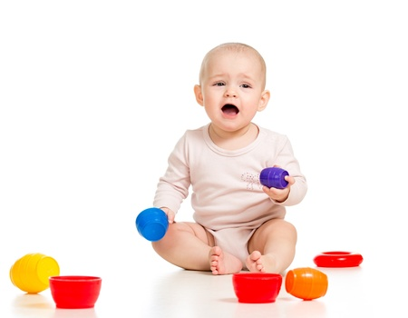 Cute baby girl playing with toys while sitting on floor, isolated over white Stock Photo - 16717449