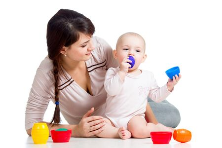 baby girl and mother playing together with colorful toys photo