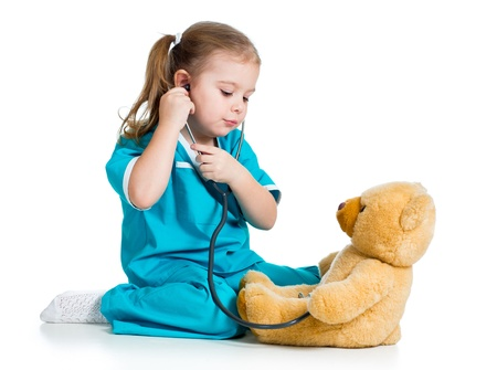 doctor s smock: Adorable child with clothes of doctor examining teddy bear toy over white Stock Photo