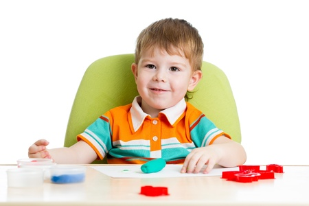 happy kid sitting at table and playing with colorful clay toy Stock Photo - 17166086