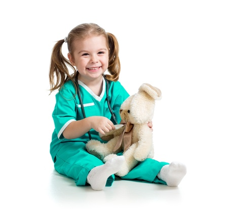 Adorable girl with clothes of doctor spoon playing with toy over white photo