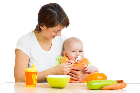 baby eating: young mother spoon feeding her baby girl isolated on white Stock Photo