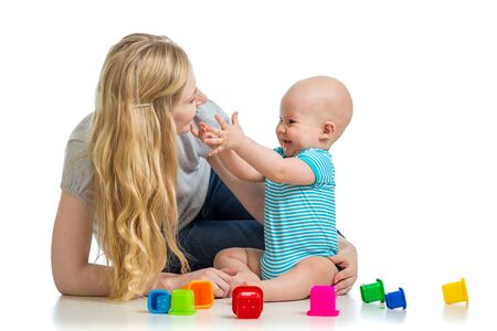 kid boy and mother playing together with cup toys photo