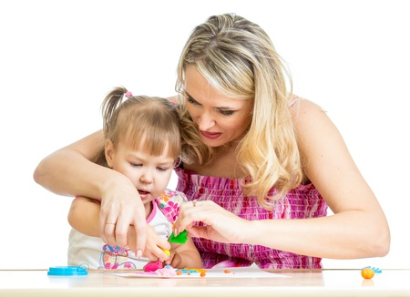 little dough: Happy little kid and mother sitting at table and playing with colorful clay toy