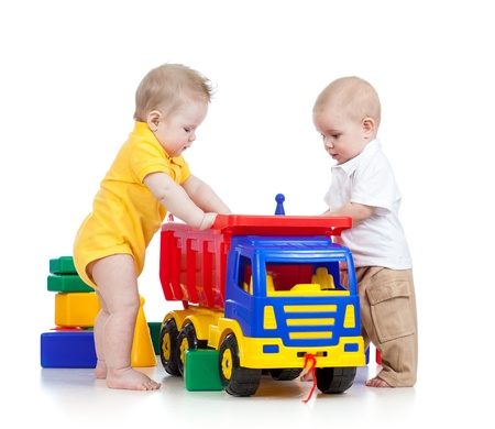 toy truck: two little children playing together with color toys