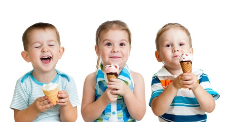 children eating: happy children boy and girls eating ice cream in studio isolated Stock Photo