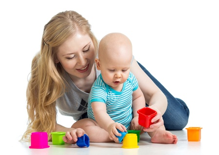 baby boy and mother playing together with colorful toys photo