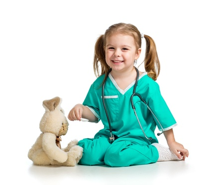 doctor s smock: Adorable girl with clothes of doctor playing with toy over white Stock Photo