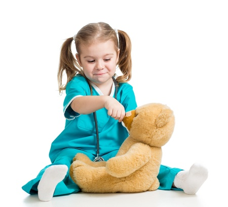doctor s smock: Adorable girl with clothes of doctor spoon feeding teddy bear over white Stock Photo