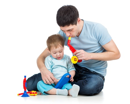 Father and baby boy having fun with musical toys   Isolated on white background photo