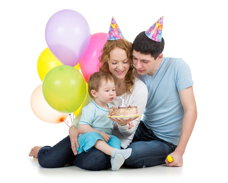 family celebrating birthday baby boy and blowing candle on cake photo