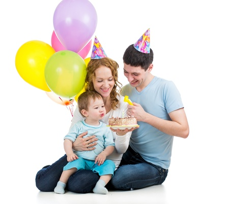 child boy with parents celebrating birthday and blowing candle on cake photo