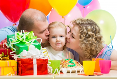 parents kissing kid girl on birthday party photo