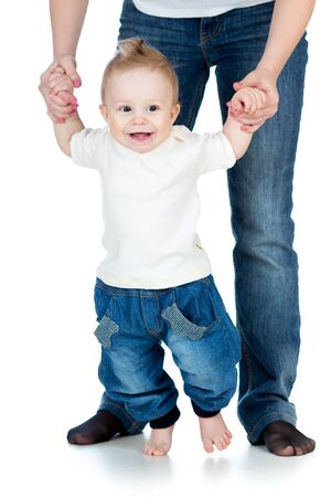 the first step: happy baby boy steps first time isolated Stock Photo