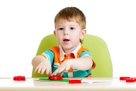 kid boy sitting at table and playing with colorful clay toy Stock Photo - 17605099