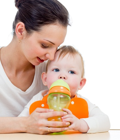 young mother giving drink to baby from feeding cup Stock Photo - 17641811