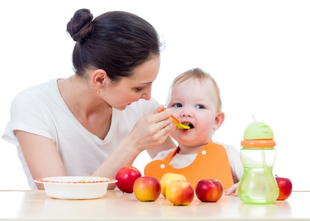 young mother spoon-feeding her baby girl photo