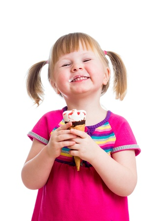 satisfied: happy kid girl eating ice cream in studio isolated