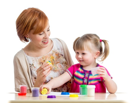 little dough: Happy child girl and mother sitting at table and playing with colorful clay toy Stock Photo