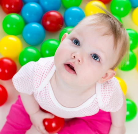 Portrait of cute baby girl playing among colorful balls photo