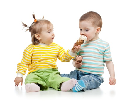 eating ice cream: babies girl and boy eating ice cream together in studio isolated Stock Photo