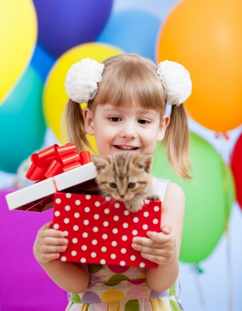 gifting: kid girl with colorful balloons and kitten in gifting box Stock Photo
