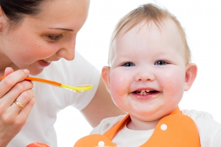 baby eating: young mother spoon-feeding happy daughter Stock Photo
