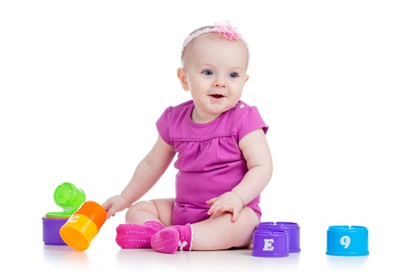 Funny baby girl playing with cup toys, isolated over white photo