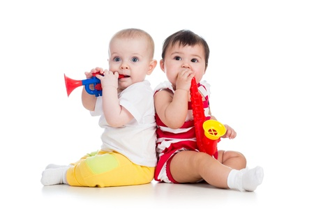 Funny babies girls with musical toys  Isolated on white background photo
