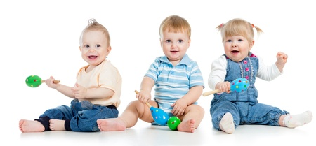 Los bebés juegan con los juguetes musicales Dos niños y una niña con maracas aislados sobre fondo blanco