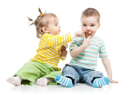 happy children little girl and boy eating ice cream in studio isolated photo