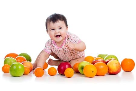 pome: happy baby girl sitting among fresh fruits