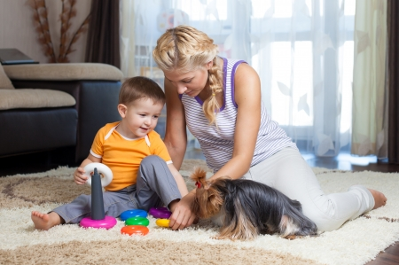 mother helping baby: mother, child boy and pet dog playing toy together indoor