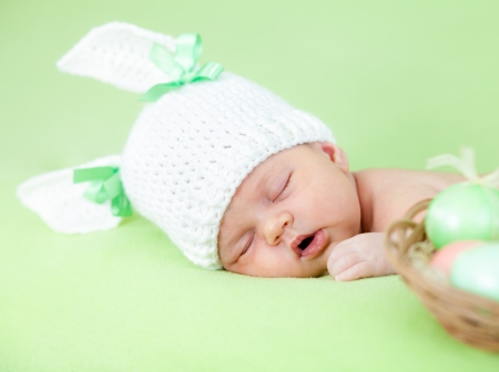 newborn animal: adorable baby dressed in Easter bunny cap with eggs